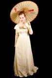 Mädchen im viktorianischen Kleid, das einen chinesischen Regenschirm hält Stockbilder