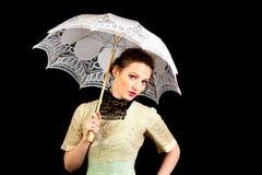 Mädchen im viktorianischen Kleid, das einen weißen Regenschirm hält Stockbild