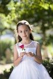 Mädchen im weißen Kleid in der Parkholdingblume Stockfotos