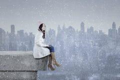 Mädchen im Wintermantel unter Verwendung des Laptops auf dem Dach Stockbilder