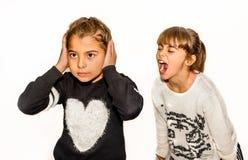 Mädchen mit acht Jährigen, das verärgert ist und an ihrer Schwester schreit Isolator Stockbild