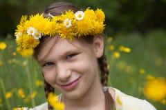 Mädchen mit Blumen auf ihrem Kopf auf einer Wiese in der Natur Stockfotografie