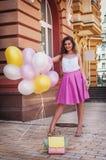 Mädchen mit buntem Latex steigt, städtische Szene, draußen im Ballon auf Stockbild