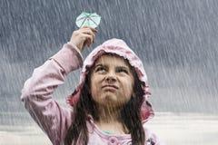 Mädchen mit Cocktailregenschirm im Regen Stockfoto