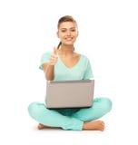 Mädchen mit dem Laptop, der sich Daumen zeigt Lizenzfreie Stockbilder