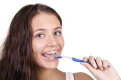 Mädchen mit den Klammern, die ihre Zähne putzen Stockfotografie