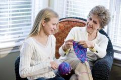 Mädchen mit der Großmutter, die in liebevollem Raum strickt Stockfoto
