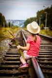Mädchen mit einem Blumenstrauß, der auf den Schienen sitzt Stockfotografie