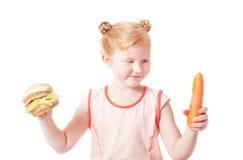 Mädchen mit Karotten und Hotdog Lizenzfreie Stockfotos