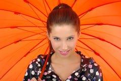 Mädchen mit orange Regenschirm Stockfotos