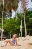 Mädchen mit zwei Zöpfen in einem Badeanzug auf einem Schwingen auf dem Strand Lizenzfreie Stockfotos