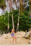 Mädchen mit zwei Zöpfen in einem Badeanzug auf einem Schwingen auf dem Strand Stockfotografie