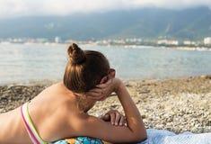 Mädchen nimmt ein Sonnenbad und betrachtet Meer Stockbilder
