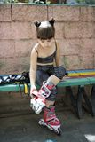 Mädchen-Schlittschuhläufer auf der Bank am Park Lizenzfreie Stockfotos