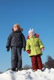 Mädchen und Junge, die am Schnee stehen Stockbild
