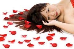 Mädchen und Rosen-Blumenblätter Lizenzfreie Stockfotos