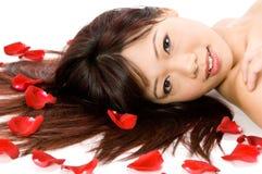 Mädchen und Rosen-Blumenblätter Lizenzfreies Stockfoto
