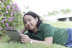 Mädchen- und Tablettecomputer, der auf Feld des grünen Grases liegt Lizenzfreie Stockfotos