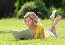 Mädchen, welches das Buch liest. Blonde schöne junge Frau mit dem Buch, das auf dem Gras liegt. Im Freien. Sonniger Tag Stockbilder