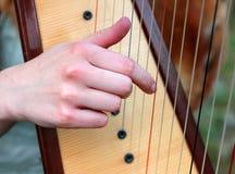 Mädchen, welches die alte Harfe zupft die Schnüre 2 spielt Stockbild