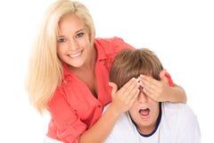 Mädchen, welches die Augen des jungen Mannes abdeckt Stockfotos