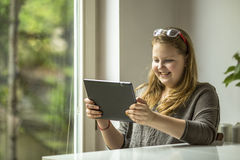 Mädchen, welches die Computerspiele sitzen am Fenster spielt Stockfotografie