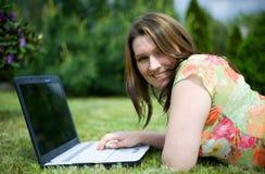 Mädchenarbeit über Laptop im Garten Stockfotos