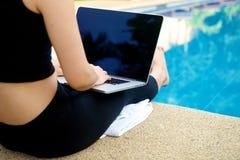 Mädchenarbeit mit Laptop am Pool Stockfotografie