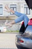 Mädchenbeine im Autokofferraum trägt Modefersen Stockfoto