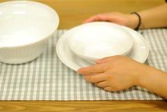 Mädchenhand, die Platten auf Tabelle anhält Lizenzfreie Stockfotos