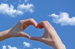 Mädchenhand im blauen Himmel der Herzformliebe Stockfoto