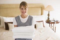 Mädchenholdingtücher beim Hotelzimmerlächeln Lizenzfreies Stockfoto