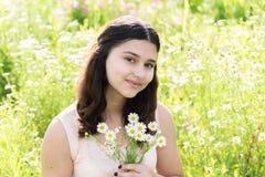 Mädchenjugendlicher mit Blumenstrauß von Gänseblümchen auf Sommerwiese Stockbild