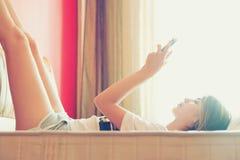 Mädchenlesetablette auf Bett Stockbilder