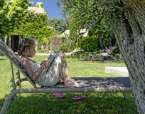 Mädchenlesung durch das Pool in Provence Lizenzfreies Stockbild