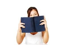Mädchenmesswert und Verstecken hinter dem Buch. Lizenzfreies Stockfoto
