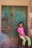 Mädchenporträt, das durch eine alte Holztür sitzt Stockfoto