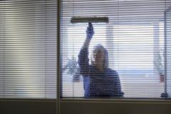 Mädchenreinigung und abwischen Fenster im Büro Stockfotografie
