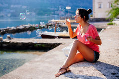 Mädchenschlagblasen auf Strand Stockfoto