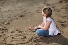 Mädchenschreibenszahl im Sand Stockfoto