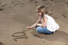Mädchenschreibenszahl im Sand Stockfotografie