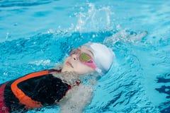 Mädchenschwimmenrückenschwimmen im Pool Stockbilder