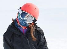 Mädchenskifahrer wickelte oben warmes im Skifahrengang mit Sturzhelm a ein Stockfoto