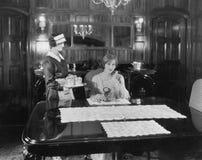 Mädchenumhüllungsfrau bei Tisch (alle dargestellten Personen sind nicht längeres lebendes und kein Zustand existiert Lieferanteng Lizenzfreies Stockbild