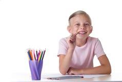 Mädchenzeichnung mit farbigen Bleistiften Lizenzfreie Stockfotos