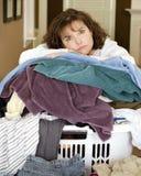 Müde Frau, die auf Stapel der Wäscherei stillsteht Lizenzfreies Stockfoto