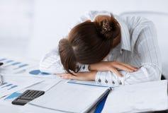 Müde Frau, die bei der Arbeit schläft Stockbilder