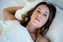 müde Frau, die im Bett anstarrt in Raum liegt Lizenzfreie Stockbilder