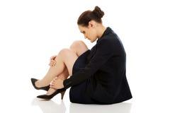 Müde Geschäftsfrau, die auf dem Boden sitzt Stockbild