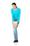 Müde Studentenfrau, die schwere Bücher hält Stockbild